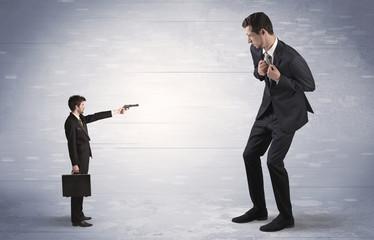 Small businessman shooting giant businessman