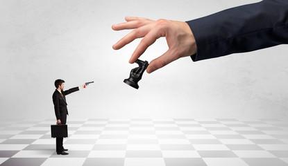 Businessman fighting against big chessman on a big hand