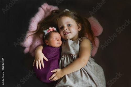 c7be67b182309 Little sister hugging her newborn sister. Toddler kid meeting new ...