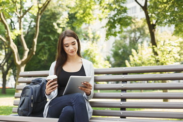 Smiling woman in park using digital tablet