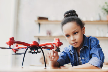 Young cute girl holding quadcopter. Child playing with drone. Education, children, technology, science, future and people concept