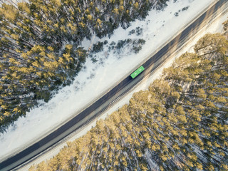 Snowy road with a moving bus in winter. Aerial photography