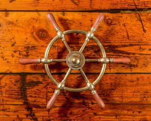 Brass Ship Wheel on Textured Wood
