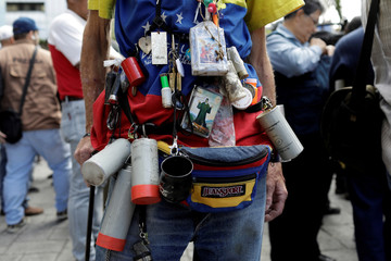 A man wears spent tear gas canisters, cartridges and other items as opposition supporters gather in front of the United Nations offices in Caracas
