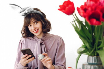 beautiful stylish girl in bunny ears smiling and painting easter eggs on rustic table and holding phone in home with space for text. woman talking photo of easter table. easter hunt