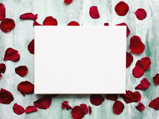 Mockup poster on wooden board with flowers petals. White canvas on stretcher. Romantic background.