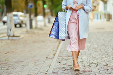 Closeup of woman holding shopping bags on the street with copy space. Happy woman with shopping bags enjoying in shopping. Consumerism, shopping lifestyle concept.