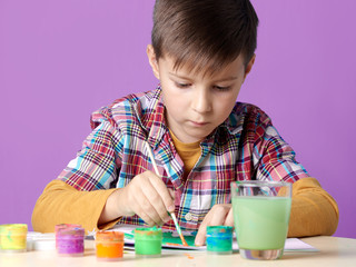 Caucasian boy is carefully painting with watercolors.