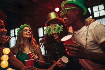 Multi-ethnic friends celebrating St. Patrick's Day in nightclub