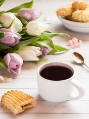 Coffee Cup with biscuits and tulips on a wooden table
