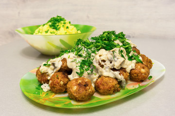 Fried meatballs with stroganoff gravy and mashed potatoes and fresh herbs on a table