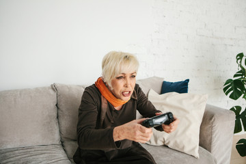 An elderly woman is playing a video game. Elderly person and modern technology.