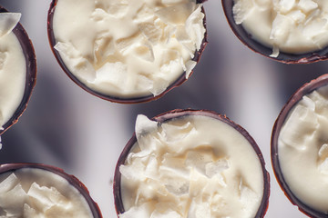chocolate sweet dessert filling with coconut cream and coconut petals on top, product photography fot patisserie