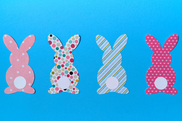 Easter bunny decoration on blue background, copy space. DIY holiday handicraft of colorful rabbits. Flat lay, top view. Border of paper rabbits cutouts. Easter greeting card. Happy Easter concept.