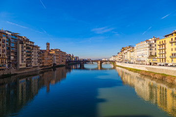 Cityscape view on Arno river with famous Holy Trinity bridge in Florence. Reflections on water. Old colorful houses on the side. Tuscany, Italy