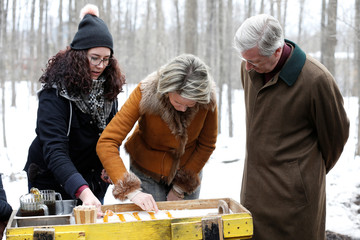 Belgium's King Philippe looks on as Queen Mathilde makes maple taffy at the Richelieu Park sugar shack in Ottawa