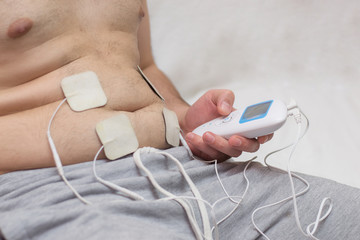a man with excess weight makes a stomach massage using an electrical muscle massager