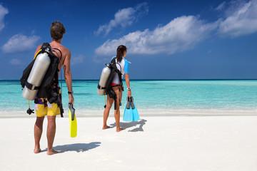 Taucher Paar mit Ausrüstung am tropischen Strand schaut auf den Ozean