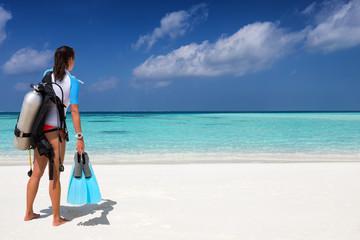 Weibliche Taucherin am tropischen Strand schaut auf den Ozean