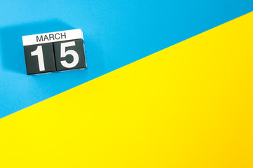 March 15th. Day 15 of march month, calendar on blue and yellow background flat lay, top view. Spring time. Empty space for text