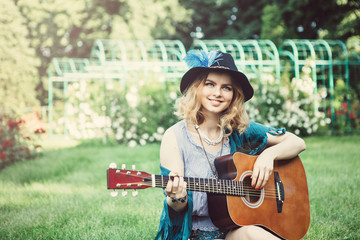 Summer holidays, vacation, travel and people concept - smiling young hippie woman with guitar playing music. Funny time for the best friends. Lifestyle. Boho style.