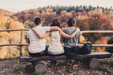 The three friends hugged each other sitting on wooden benches and watch the beautiful autumn landscape Wall mural