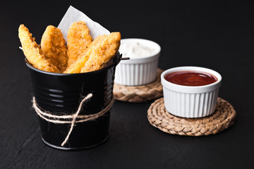 Fried chicken dippers in black bucket with sauce