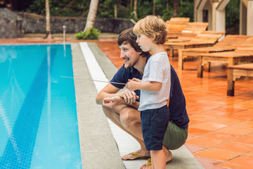 Father and son playing with a remote controlled boat in the pool