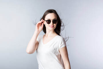 Smiling woman in sunglasses and hair wind on a gray