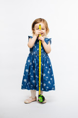 A smiling preschool girl holding a measuring tape in front of her