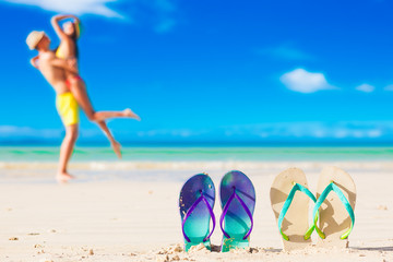 picture of two flip flops with young couple on beach background