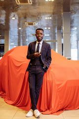 happy african car salesman using smart phone in showroom