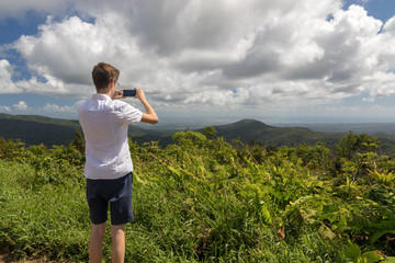 Teenager taking picture of a tropical landscape in Guadeloupe, Caribbean. Morne a Louis viewpoint towards Grande-Terre. Travel and freedom concept.