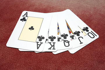 Clubs royal flush isolated over red background
