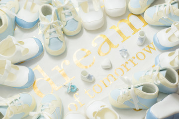 Baby boy blue bootees frame on a white cloth background. Welcoming newborn shower party. Dream of tomorrow. - top view.