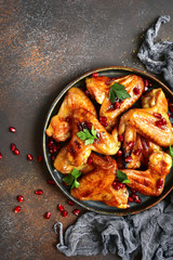 Grilled chicken wings in a honey orange glaze with pomegranate seeds.Top view with copy space.