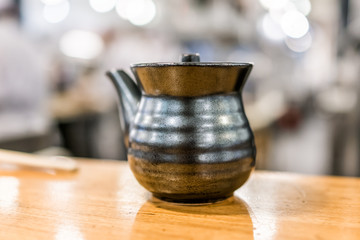 Macro closeup of traditional black clay Japanese teapot pot cermaic porcelain on wooden table in cafe restaurant isolated