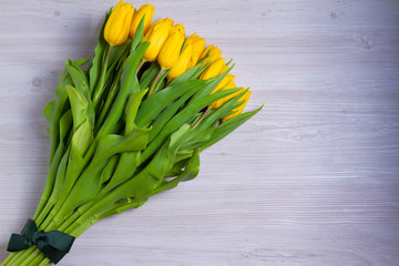 Bouquet of spring tulips flowers on white wooden background with a blank space for text. View from above, top, flat lay