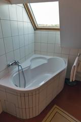 Modern bathroom with corner bath and window.