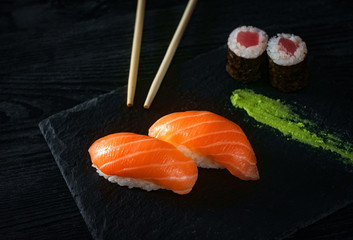 two sushi with salmon on stone