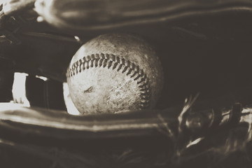 Baseball ball in game glove, dirty in monochrome for american sports image.