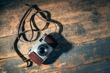 Old camera on wooden background.