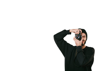 Stylish digital photographer with a beard in black shirt and casual hat. Isolated on white background, white place for your descripition concept.