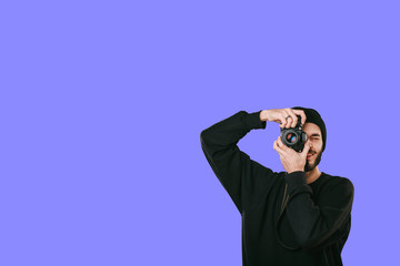 Stylish digital photographer with a beard in black shirt and casual hat. Isolated on blue background, white place for your descripition concept.