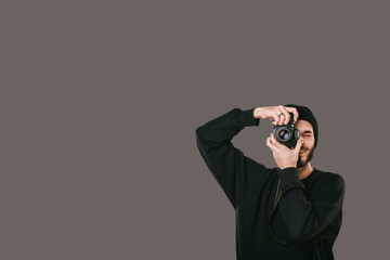 Stylish digital photographer with a beard in black shirt and casual hat. Isolated on grey background, white place for your descripition concept.