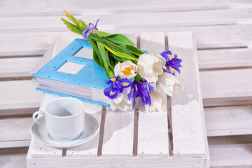 Spring background!A bouquet of irises, photo album and a cup on a wooden background.