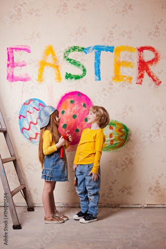 A Boy And A Girl Draw On The Wall The Word Easter And Spring Easter