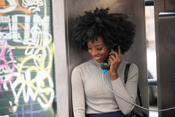 Woman talking on public pay phone