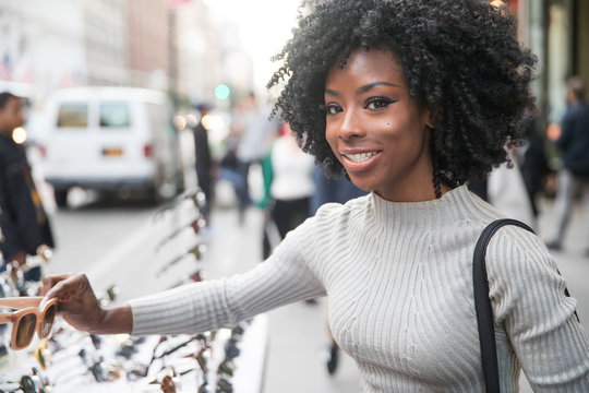Beautiful girl with black curly hair shopping for sunglasses in city