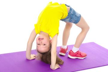The little gymnast performs a bridge.